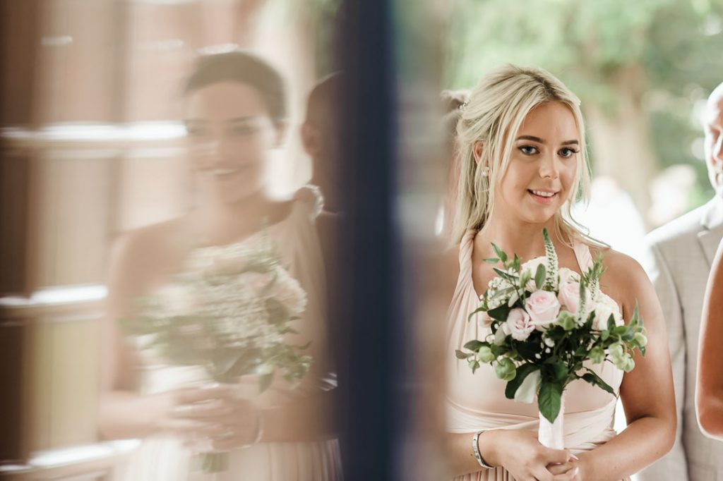 bridesmaid holding pink flowers inside church