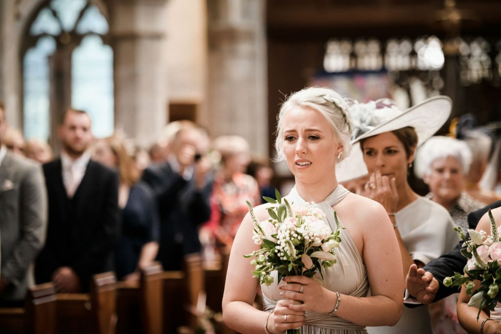 bridesmaid in blue dress walking down aisle