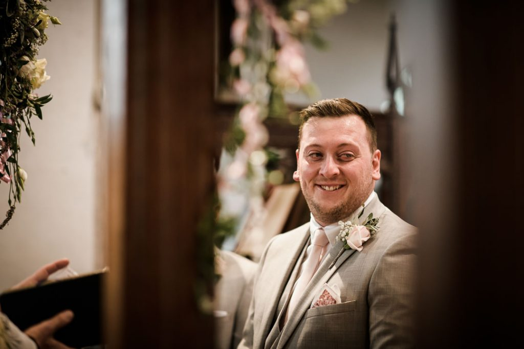 groom smiling at alter of church