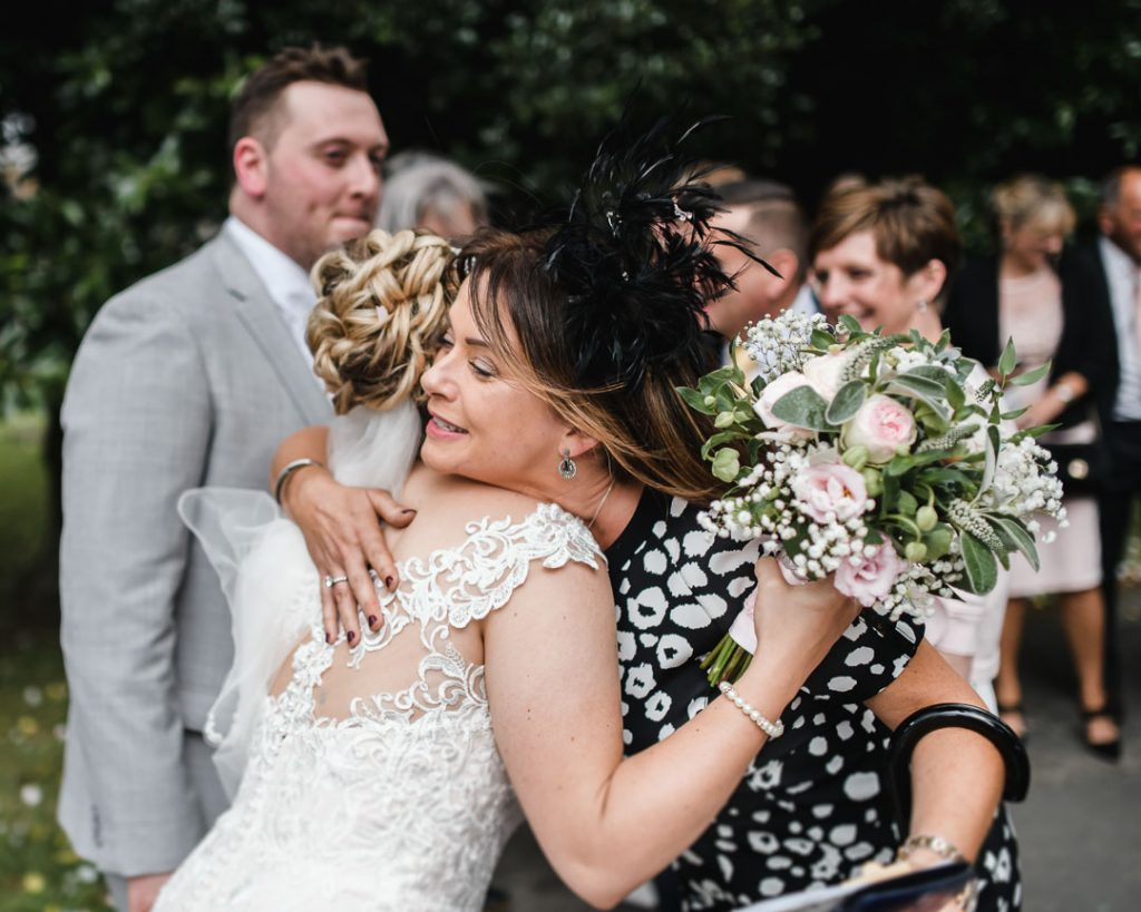 wedding guests hugs bride