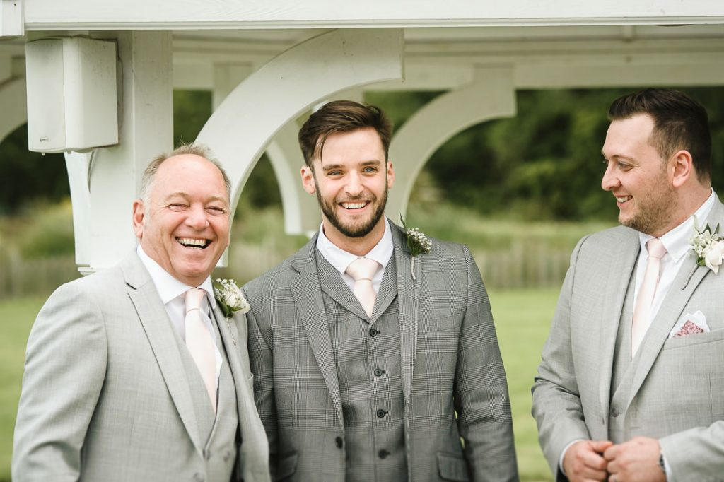 man in grey suit laughing at wedding