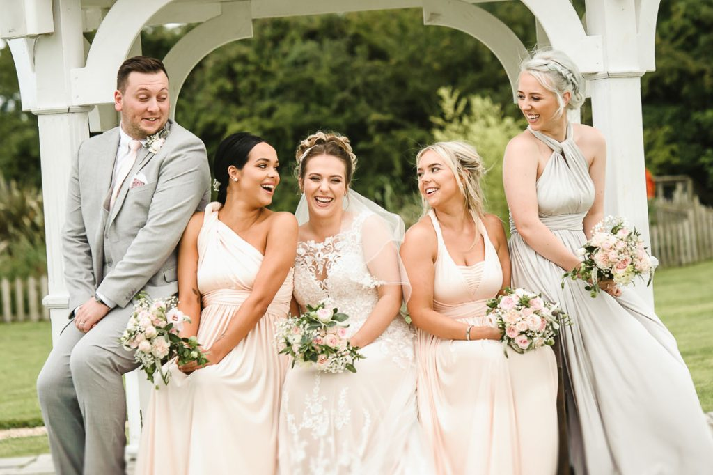 bridesmaids sat on bench laughing at each other