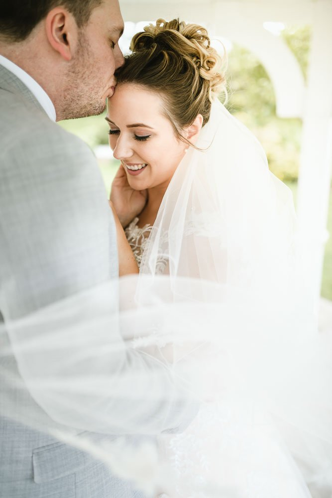 groom kissing bride on face