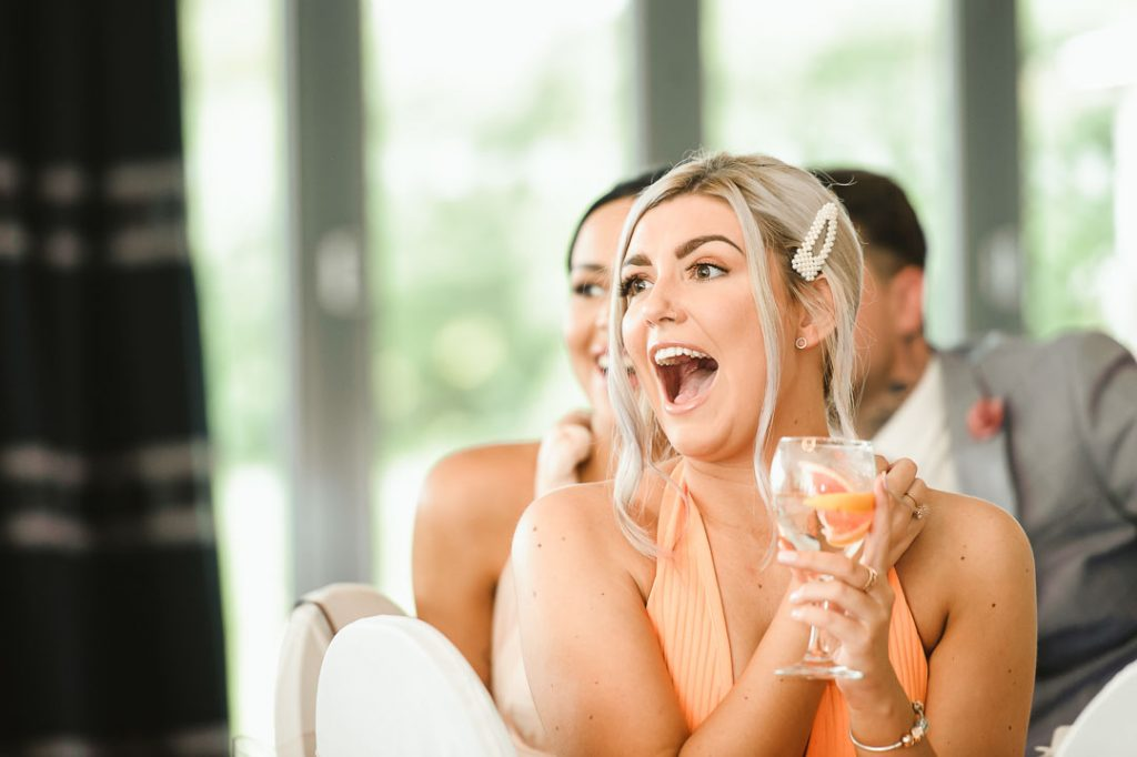 girl in orange dress laughing at wedding reception