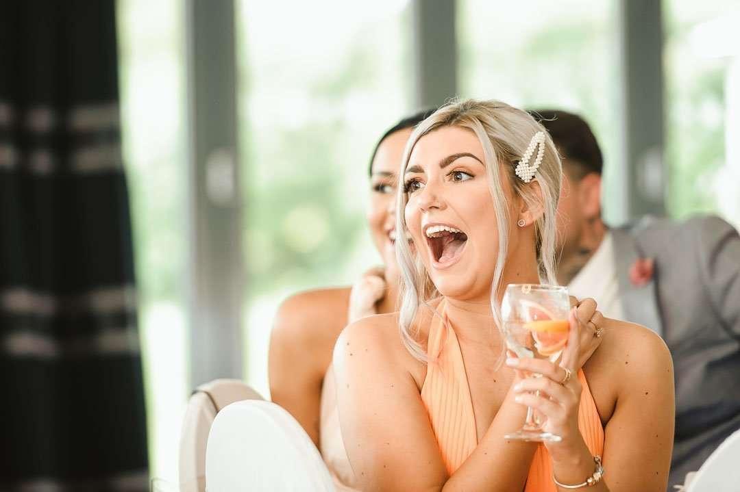 girl in orange dress laughing at wedding reception