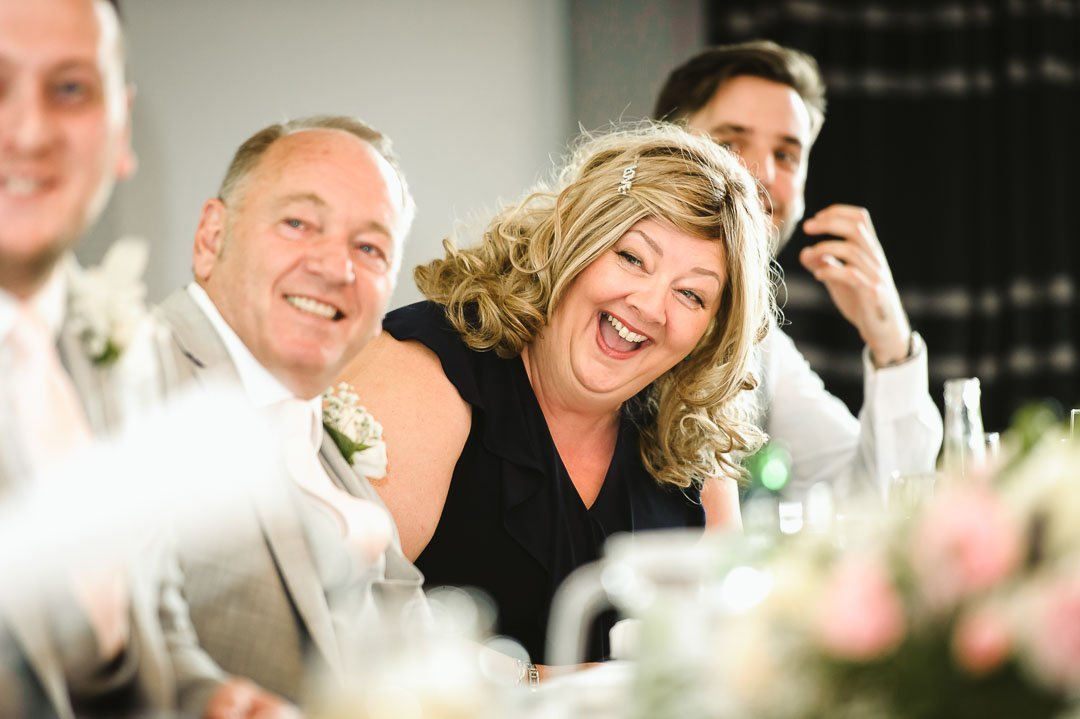 mother of bride in black dress at wedding reception laughing