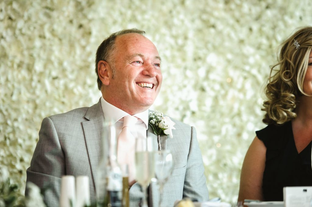 father of the groom in pink tie and grey suit smiling