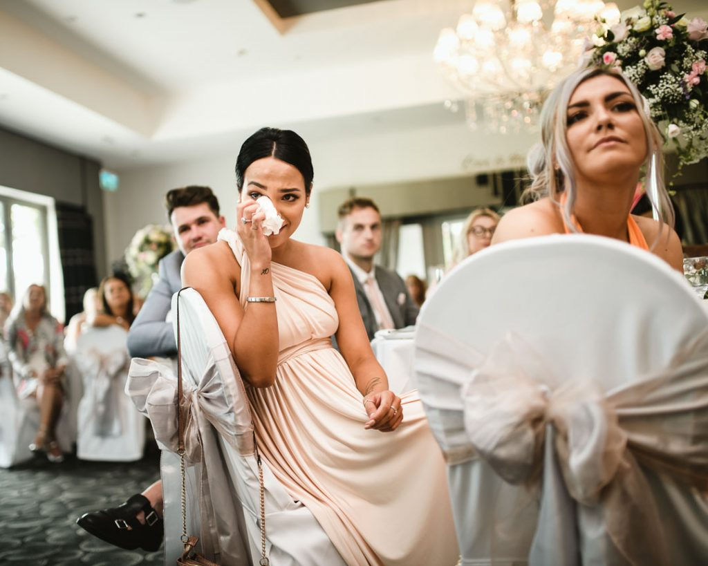 woman crying at wedding with tissue in hand