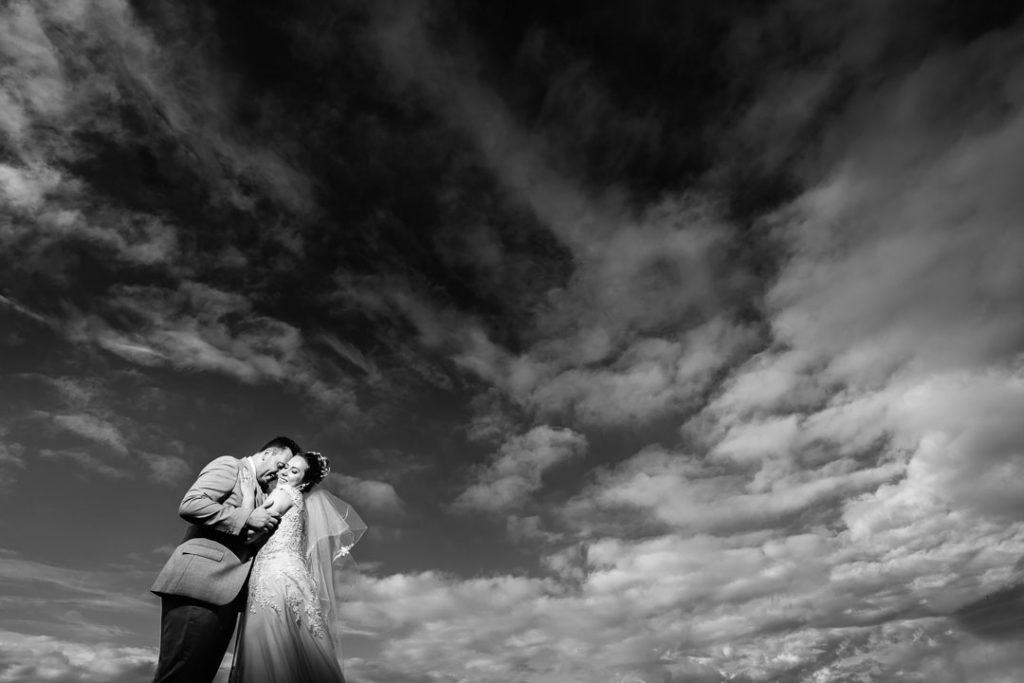 bride and groom standing against cloud background