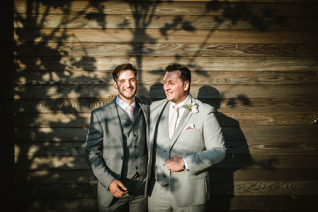 two men in grey suits laughing at wedding reception