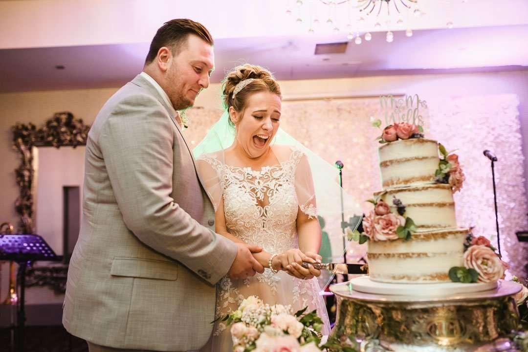 bride cutting wedding cake