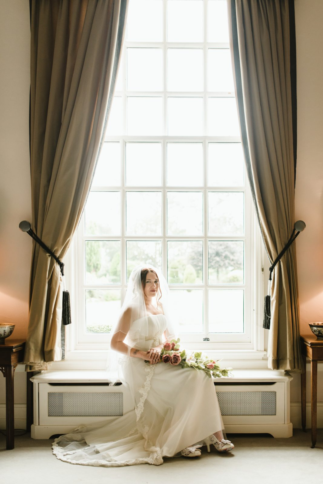 bride sat on windowsill at hemswell court wedding