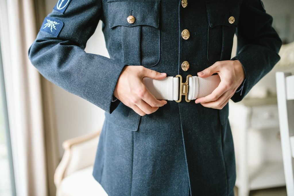 groom adjusting belt at wedding in military uniform