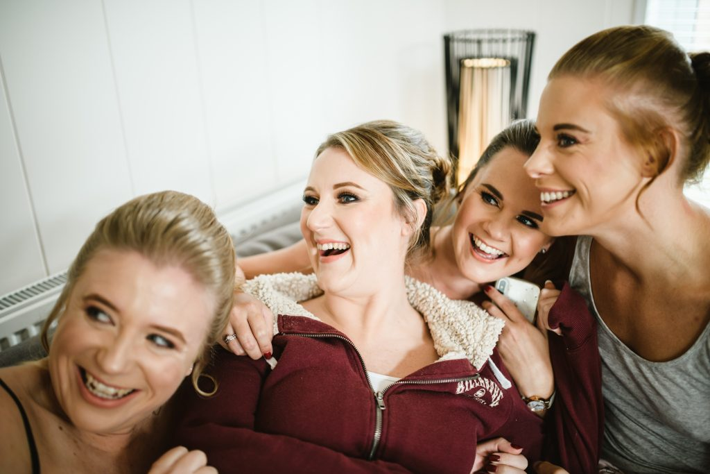 bridesmaid laughing before getting ready sat on sofa