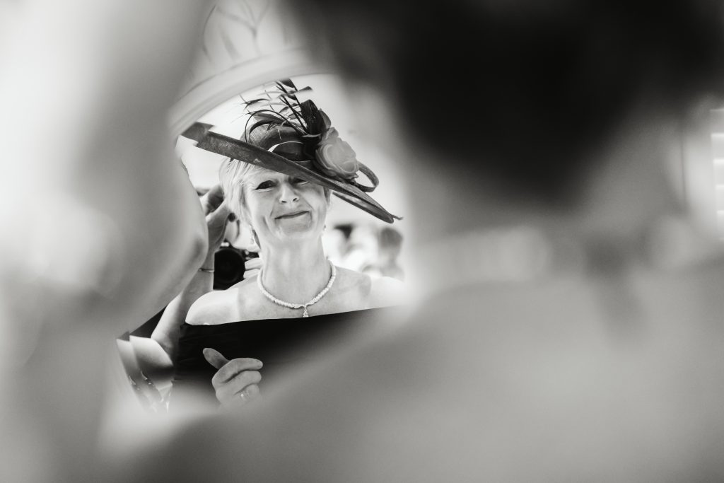 mother of the bride putting hat on