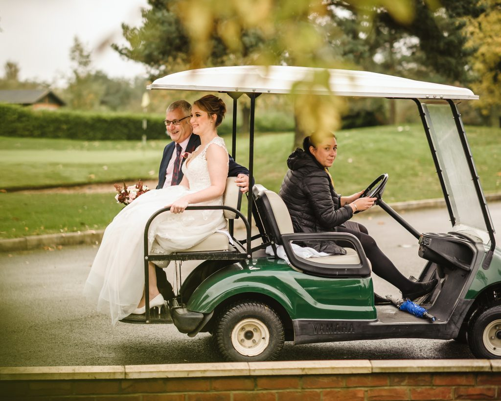 bride and father of the bride riding on golf cart