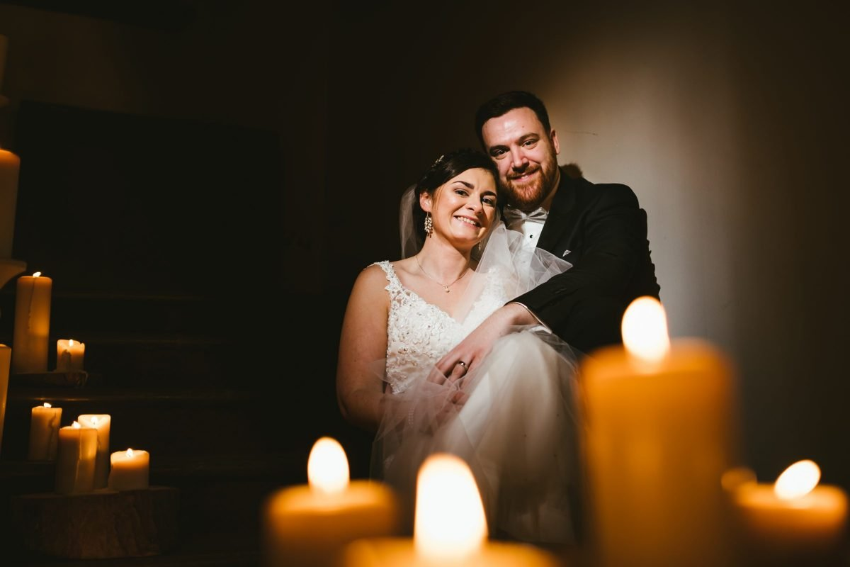 bride and groom sat on stairs under candlelight