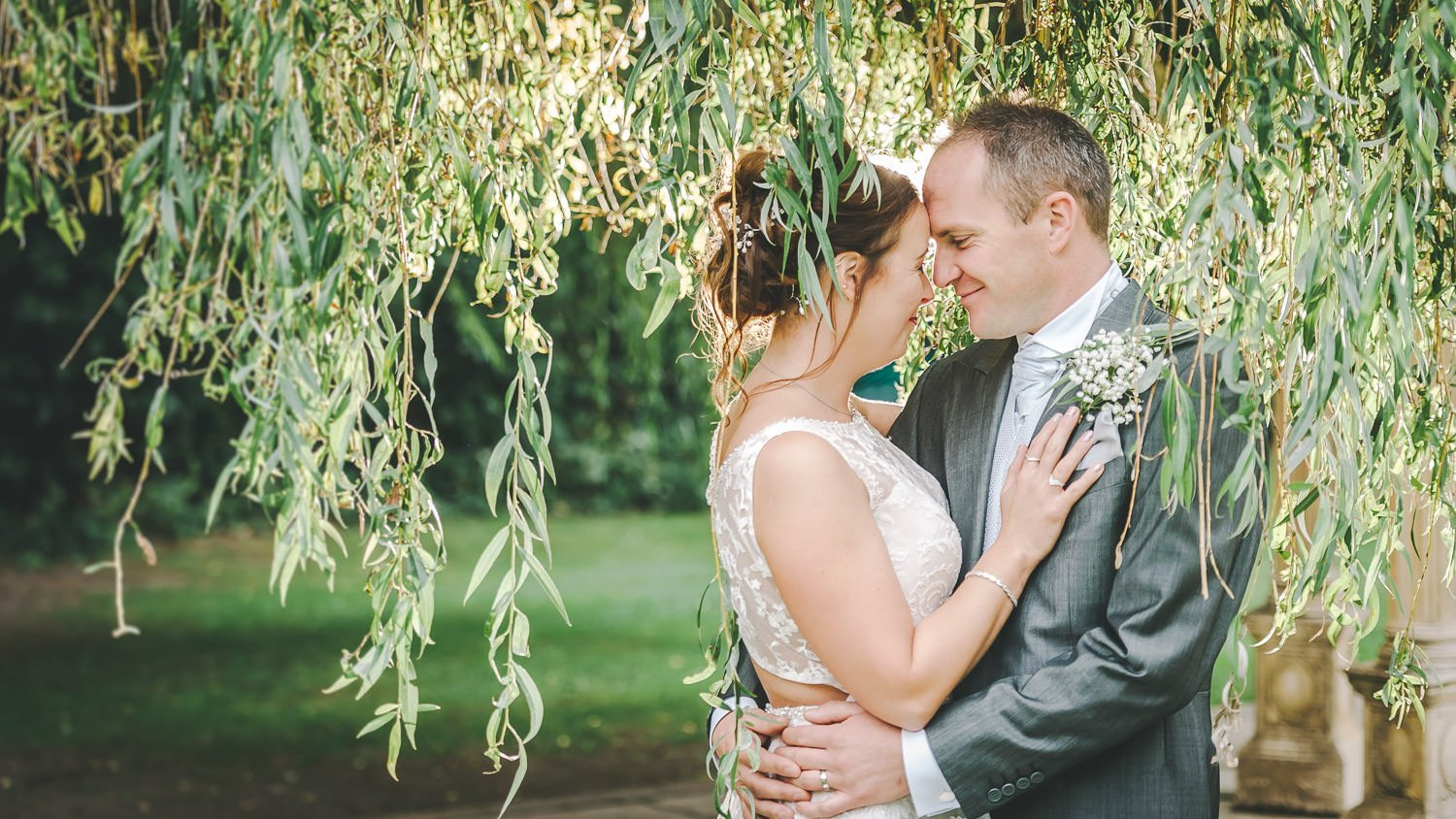 bride and groom under weeping willow at dower house hotel wedding