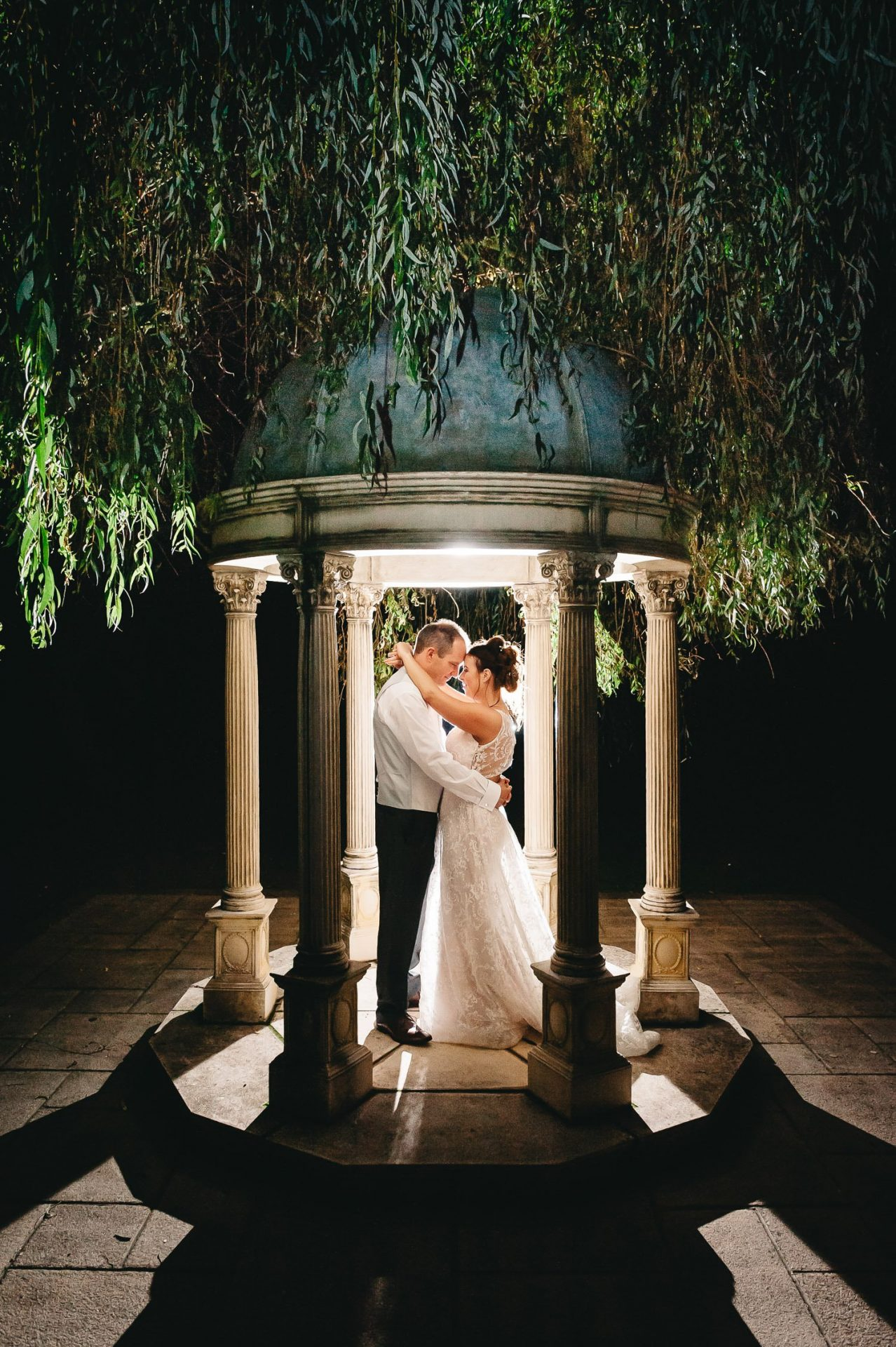 bride and groom backlit under stone folly at dower house hotel wedding