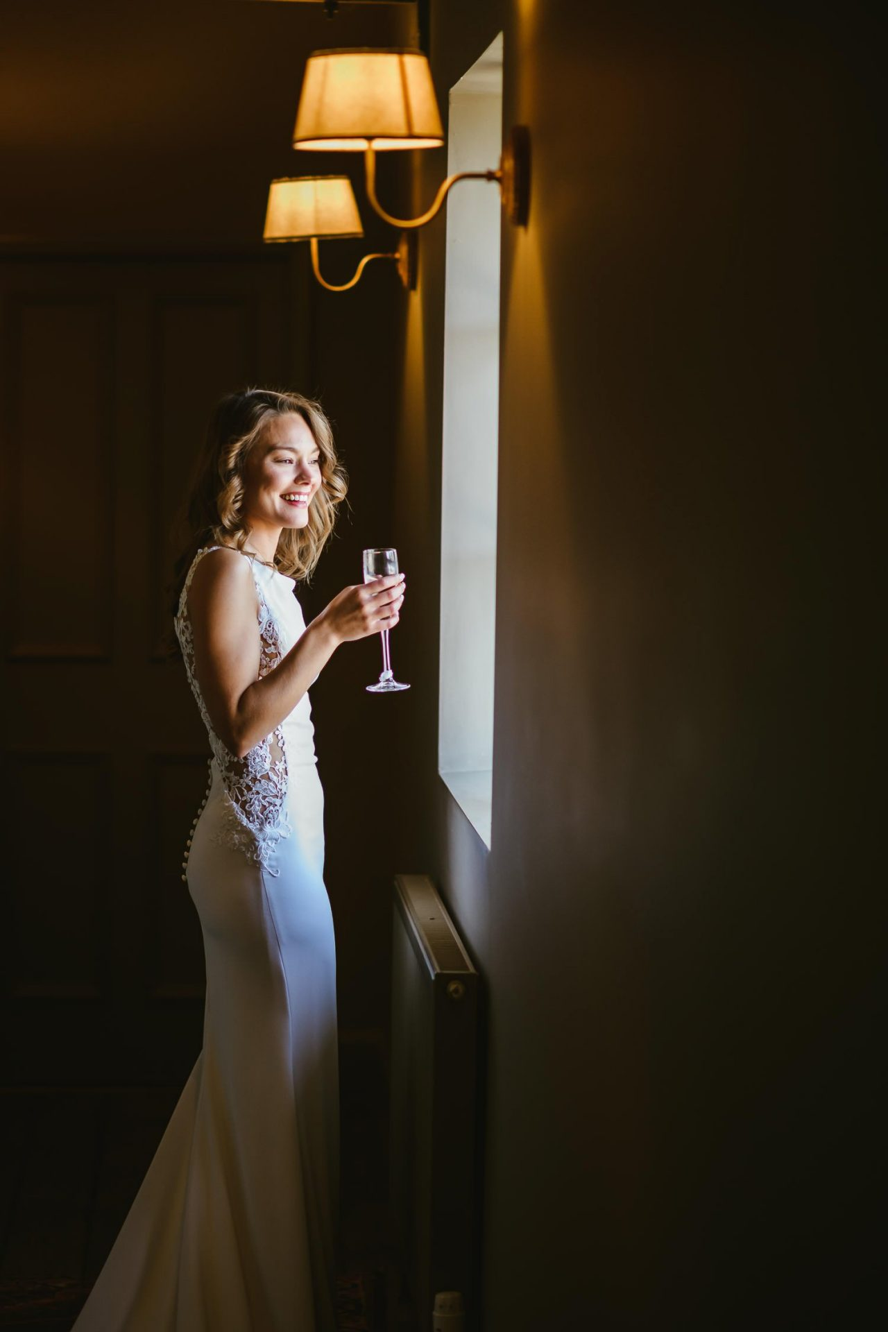 bride looking out of window at doddington hall wedding