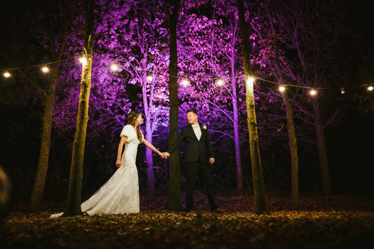 bride and groom stood under purple trees