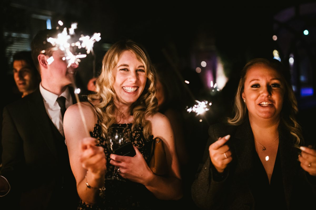 woman holding sparkler at wedding